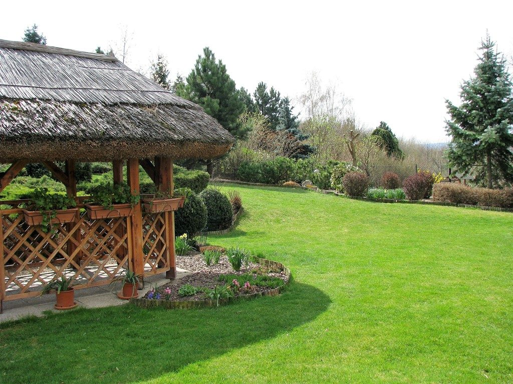 Rozľahlý-trávnik-vo-veľkej-záhrade-na-miernom-svahu-lemujú-výsadby-vytvárajúce-súkromie-1024x768